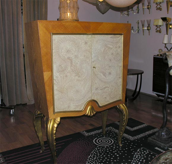 Nice cabinet by Maison Jansen with decorated parchment doors on gilded cabriolet legs.
