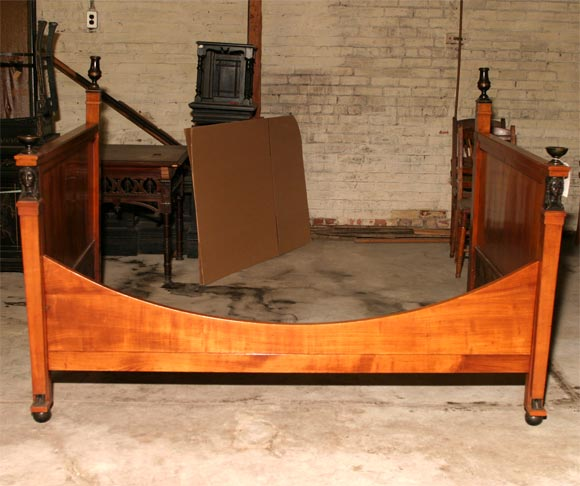 Empire fruitwood alcove bed with ebonized carved wood caryatid heads, feet and two pairs of urns.