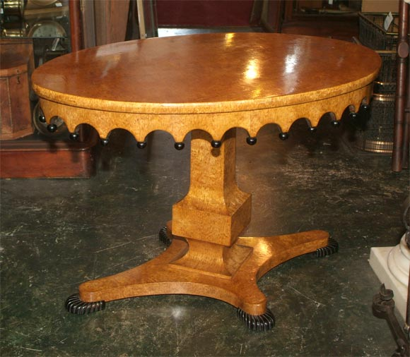 Highly figural honey colored burl wood Biedermeier style elliptical-shaped center table with ebonized ribbed feet and decorative detail. We believe this to be Amboyna wood (an exotic wood from Southeast Asia). Russia, 19th century.