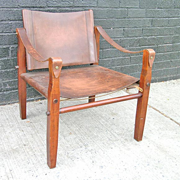 Old and orignal wood and patina'd leather Safari chair.  The chair's simple design allowed explorers a comfortable, elegant, easily transportable chair. The wonderful distress on the thick saddle leather seat and armrests suggest an active life