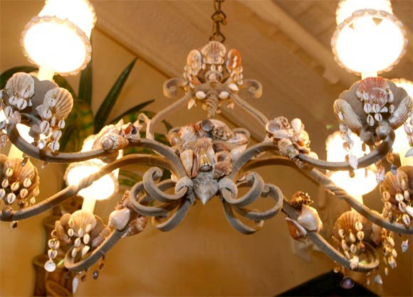 A vintage French wrought iron six-light scrolled arm rectangular chandelier encrusted in sea shells. The wrought iron carriage is covered with sand and decorated with masses of shells and shell drops, the custom-made shades are edged in tiny shells