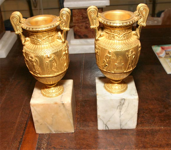 A pair of gilt bronze Grand Tour urns mounted on marble bases.