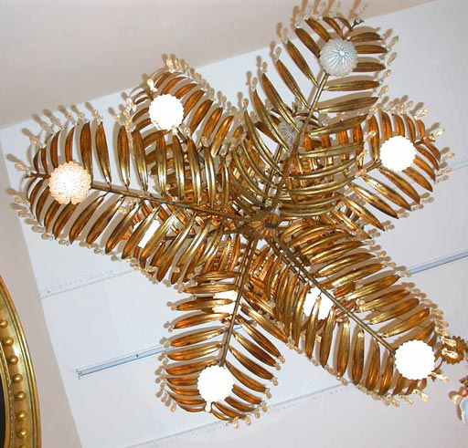 Gilt metal palm frond-form chandelier with multiple drop prisms and eleven lights contained within beaded glass sleeves.