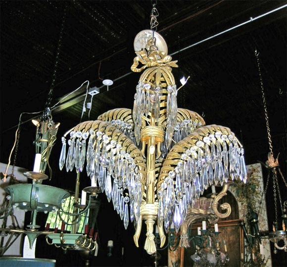 Two tier palm frond bronze chandelier with hanging crystal prisms.