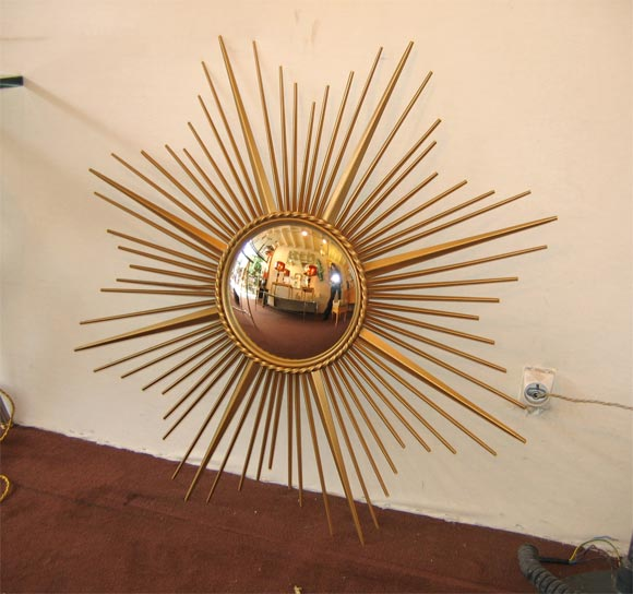 Convex mirror with a brass frame imitating the sun rays.