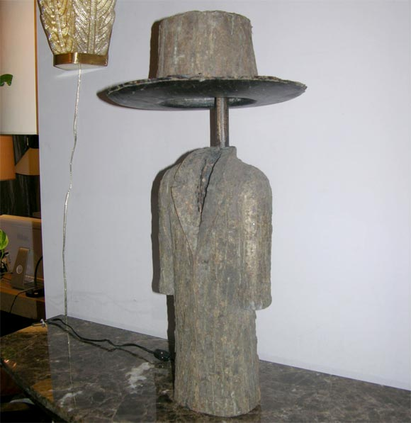 A pair of sculptural wood coat and top hat lamps.