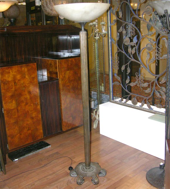 A wrought iron standing floor lamp stamped by Edgar Brandt (1880-1960), from circa 1925, with alabaster shade.