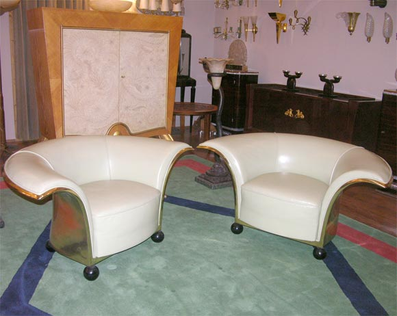 Created in 1935 for the Canadian Embassy at the Hague, upholstered in light green leather, with polished brass back and lacquered wood spherical legs.