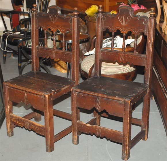 Set of four pine dining side chairs with carved spindles and backrests. The seats are pine plank standing on square legs. With original patinated finish. Spanish Colonial, circa 1820.
