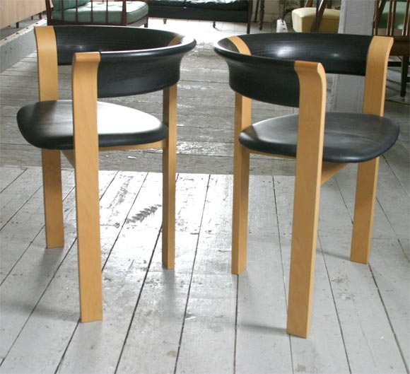 """A pair of armchairs by Rud Thygesen and Johnny Sorensen. """"The distinctive feature of this chair is its arm design. What appears to be a simple laminate wood arm is curved, thick, laminated wood. The three legs are also made of laminated wood."""" ref:"""