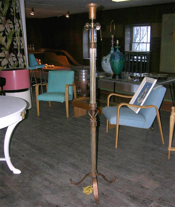 Gilt wrought iron with tubular glass rods and tripod base floor lamp from France.