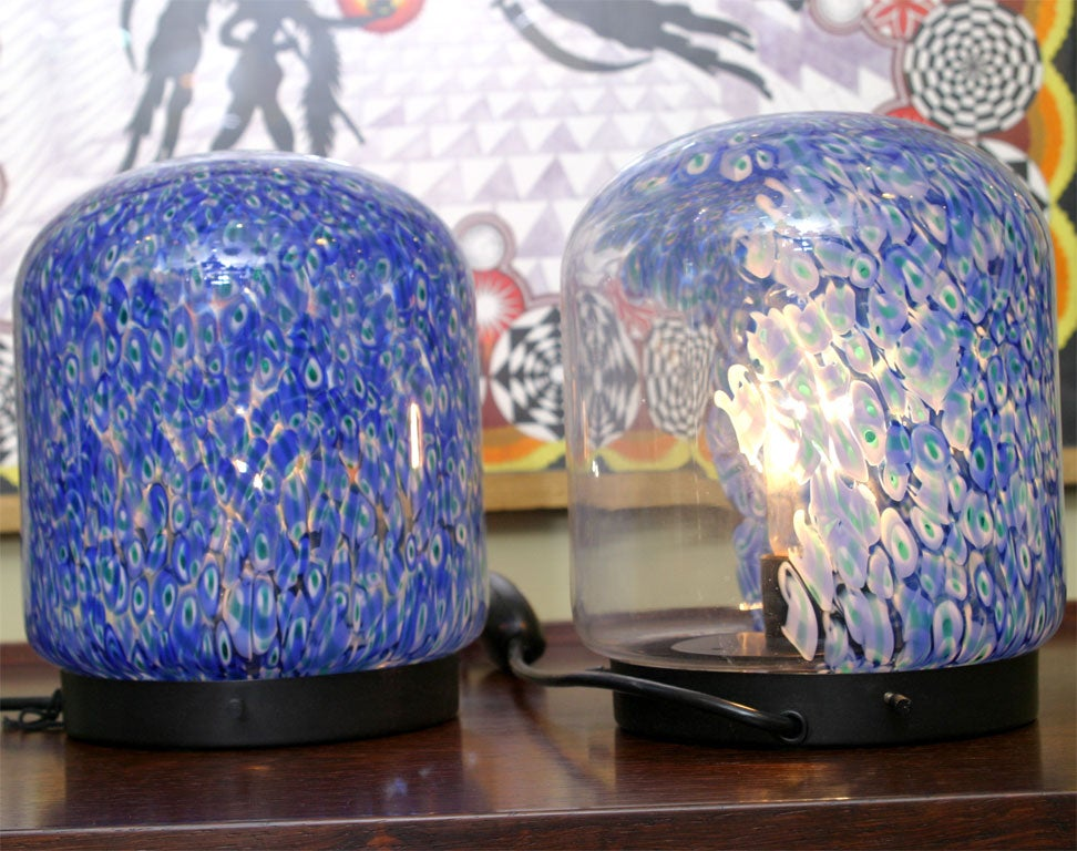 Vistosi Murano spherical Murrine and clear glass globed table lamps with round black metal socle bases. Designed by Gae Aulenti, blown glass of Serie Neverrino. Newly rewired with on cord dimmer switch. Approximately 1/3 of the back of the globe is