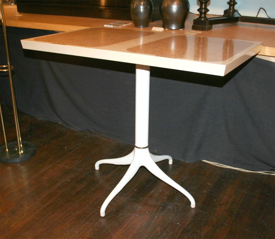 Unusual rectangular top on a pedestal base with four Legs. Top of washed wood with inset burl. White painted metal base.