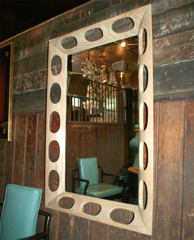 Large rectangular limed oak frame with oval cutouts. Original mirror.