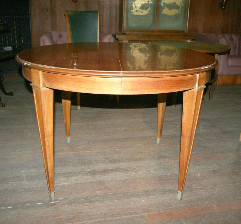 Round extention table (no leaves) with bronze trim and bronze feet.