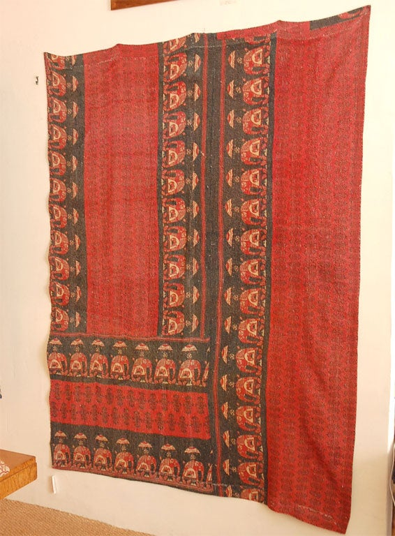 Dark blue, red and yellow pieces of old Indian textiles sewn together.   Elephant design on border. Closely sewn rows of white stitching.
