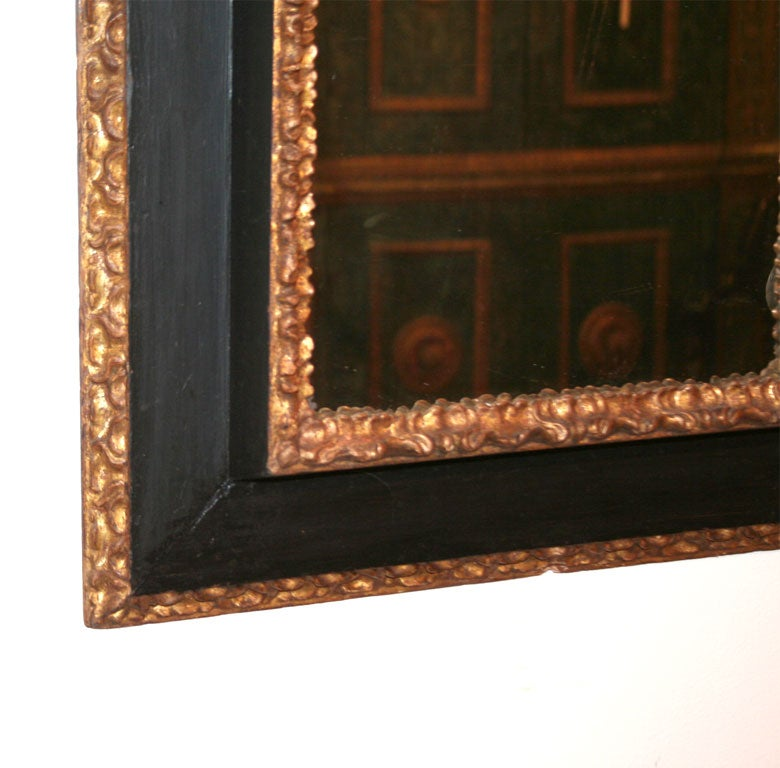 17th century Italian Baroque black painted frame with carved giltwood exterior and interior moldings.