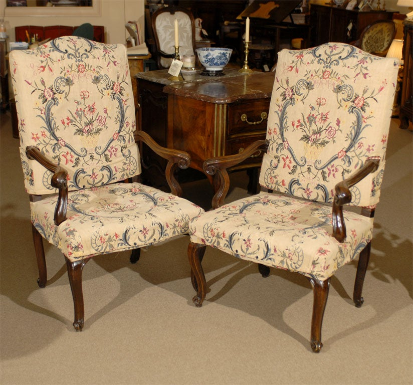 A pair of Italian Rococo period Fauteuils, with Needle-point Linen Slip Covers over a carved walnut frame.   **This is one pair of three such available, all with matching needle-point covers, serpentine back-rests, and with identical dimensions.**