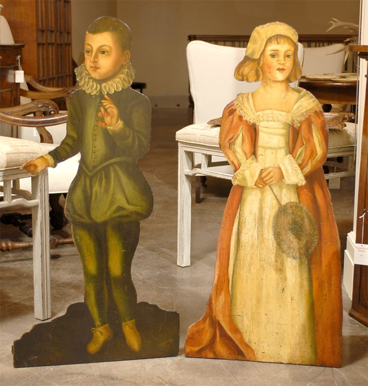 A pair of mid-19th century Victorian dummy boards composed of two life-size flat wooden figures, cut-out and painted in a beautiful and illusionistic manner, depicting a middle-class girl and boy in early 17th century English costumes. The boy is