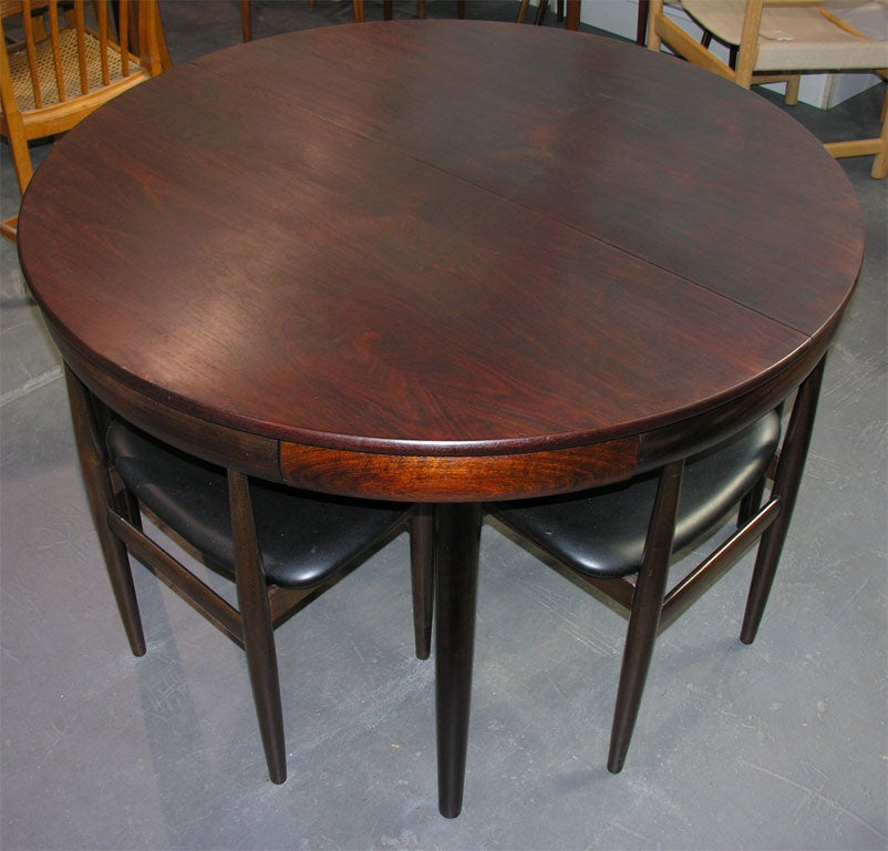 Rosewood dining table with nested chairs by hans