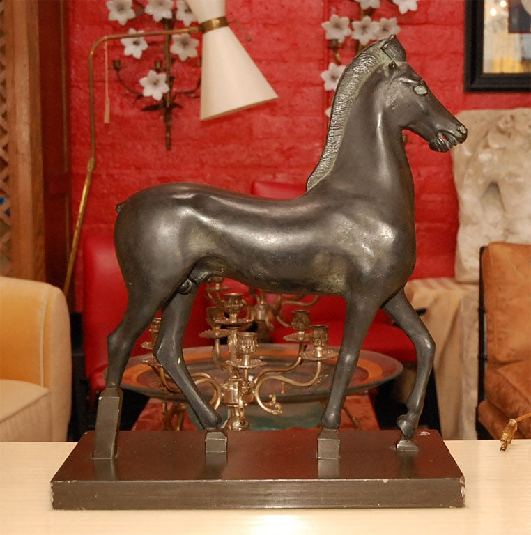 Elegant sculpture of horse with dark brown patina.