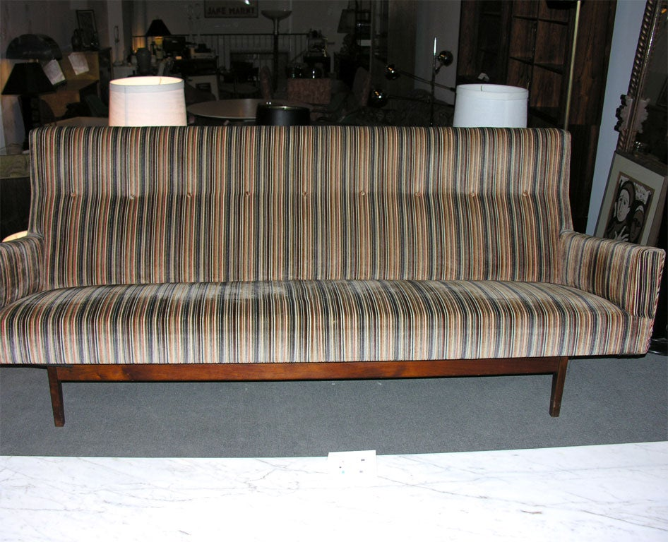 A Classic floating three seat sofa in striped velvet fabric over a tapered leg walnut frame by Jens Risom, American, circa 1950.