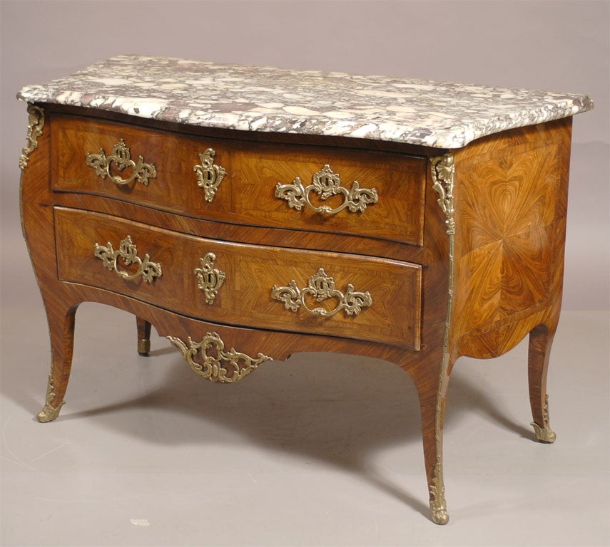 A Louis XV Style French commode with a rich arranged Kingwood & tulipwood exterior, mounted with gilt-bronze fixtures and Rococo accents, dating from the mid-1800s.   The bombe-form body with a conforming serpentine marble top, and composed of two