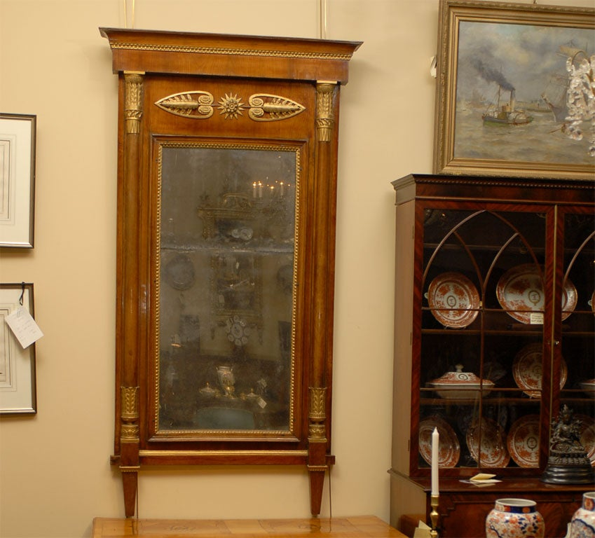 A fine and large Empire period mirror, dating from the early 1800s and French in origin.  The mirror frame in cherrywood with carved gilded neoclassical design and mirror plate in 2 parts ending with two conical feet.