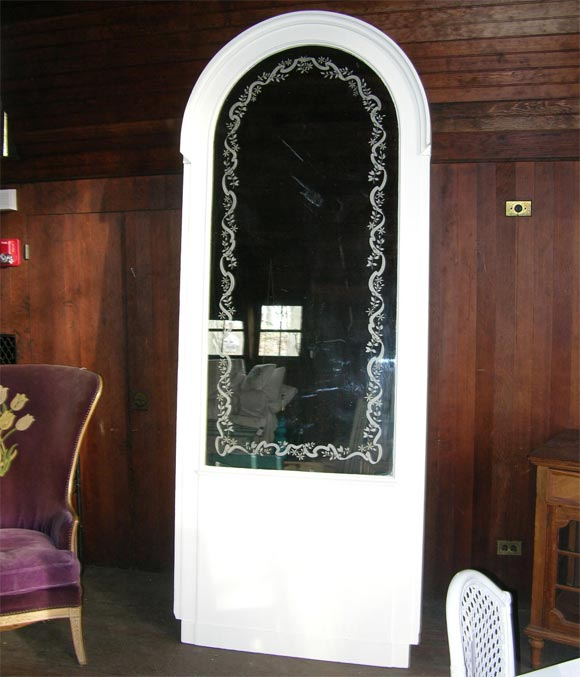 French Boiserie panel containing an arched mirror with vine and ribbon motif etching.