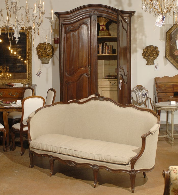 A French, Louis XV style walnut canapé from the mid-19th century, with wraparound back, scrolled arms, cabriole legs and new beige upholstery. This French canapé features a delicate wraparound back, adorned with a shell-carved crest as well as tall,