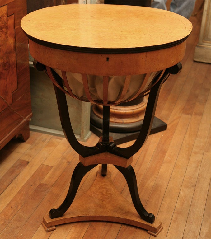 A very nice work table with a fabric basket in an open work surround. The compartmentalized interior surrounds the drop through to the basket and retains its original pin cushion. When closed it makes a great end table or occasional table. The