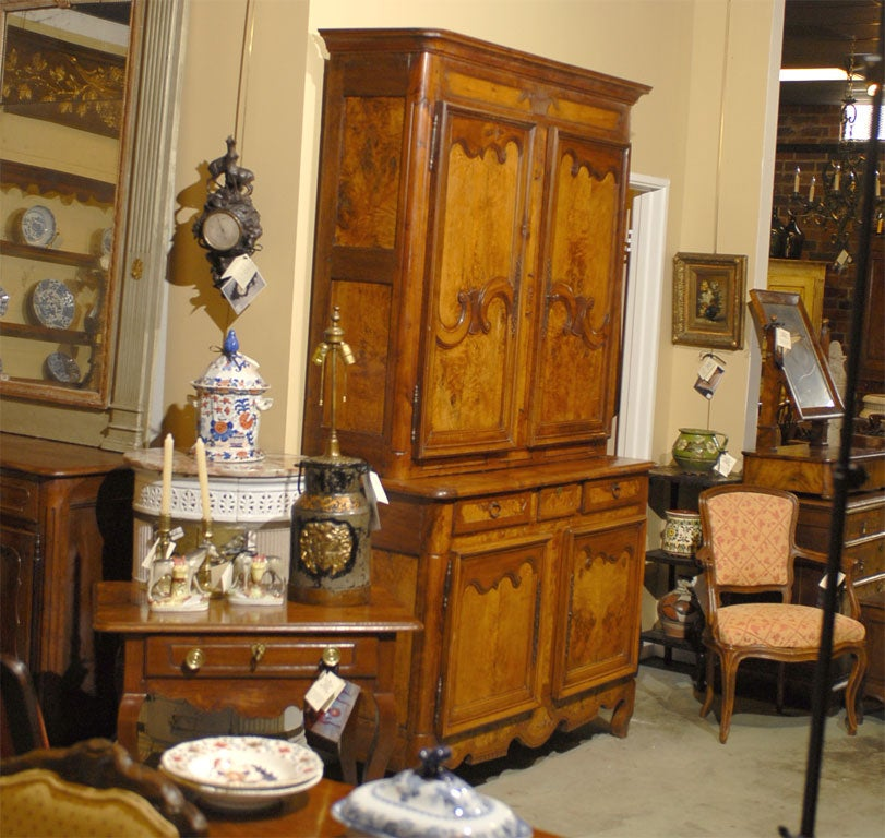 A fine Louis XV period buffet deux Corps, constructed in burled ash and cherry, with a gorgeous aged color and paneled doors on both sections. The cabinet with interior shelving, and mounted atop a shaped apron and cabriole feet.