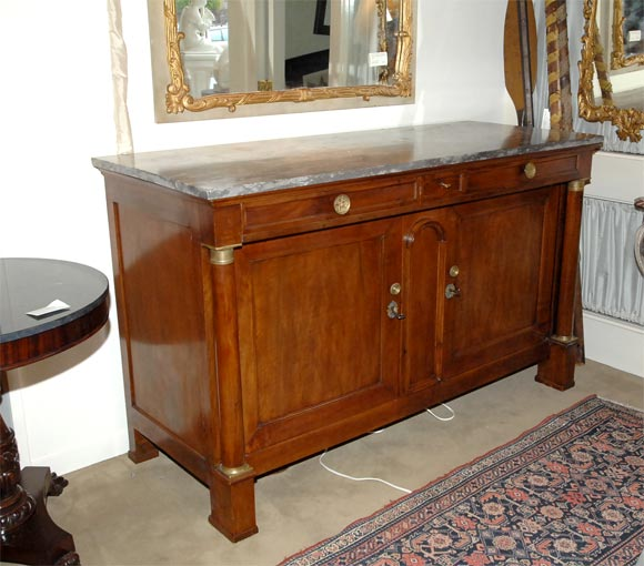 A large scaled French walnut Directoire period buffet with ormolu mounts and a gray marble top. Lots of storage.
