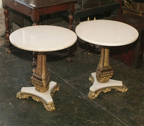 Pair brass and bronze side tables with white marble top.  The triangular repousse brass center support sitting on white marble and gilt bronze base. European, late 19th Century.