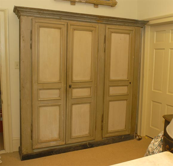 A painted French country cupboard with double doors and a matching single door on the right. The cornice is separate and the hardware is original, with the original key, 19th century.