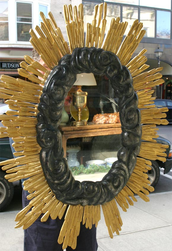 A gold and silver gilt carved wood sunburst mirror.