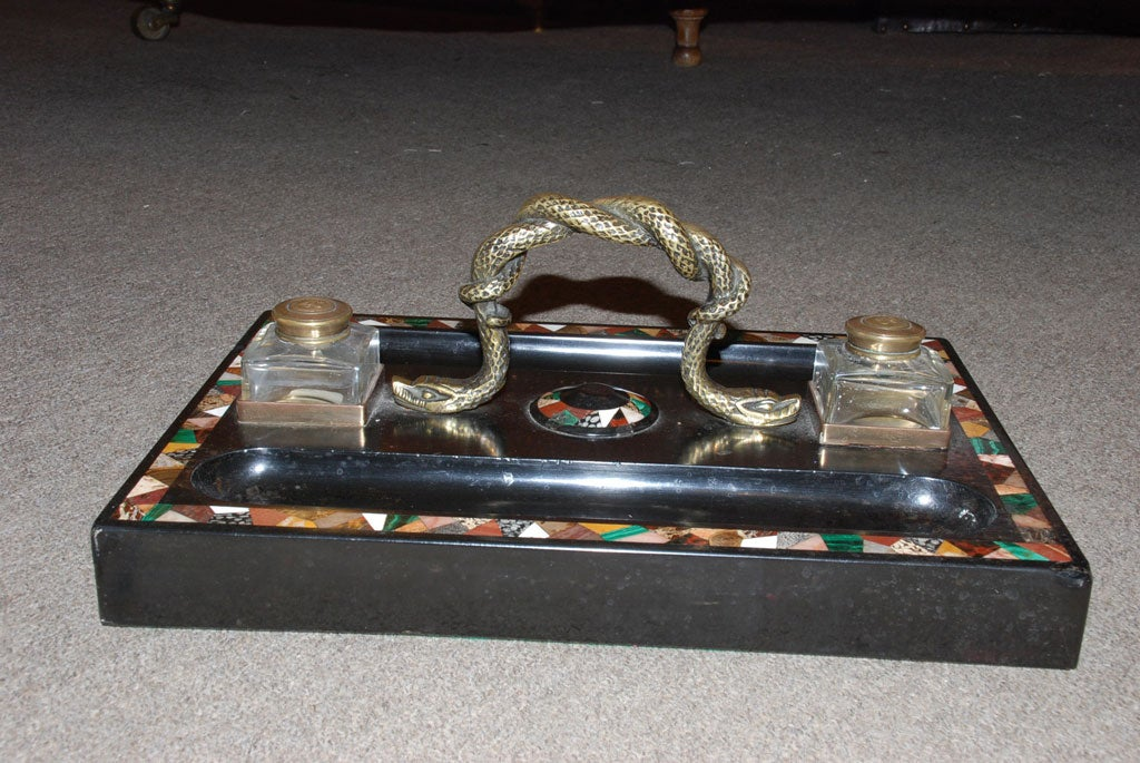 Large English Regency inkstand for a partner's desk with a bronze handle of entwined serpents. The matching blown crystal inkpots have lids with embossed crowns. The Pietra Dura band on the base is set into Belgian black marble. The inlay consists