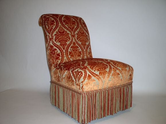 French Napoléon III style scroll-back slipper chair; upholstered in fine cut velvet with fringe trim.