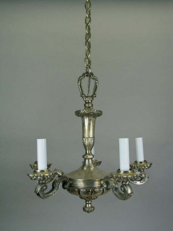 # 1-1201 this five lights chandelier has a silver plated finish. The heavily scrolled arms radiate from an ornately cast center piece.   No additional discounts.