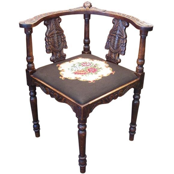 antique angel carved corner chair with old needlepoint at