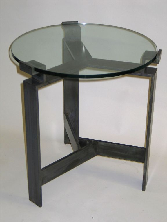 Elegant pair of French Mid-Century Modern Style side tables in bronzed hand wrought iron influenced by Art Deco and modern neoclassical sensibilities. The tables feature a unique cross braced wrought iron stretcher which supports the tripod leg
