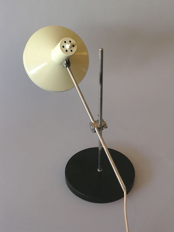An elegant Italian Mid-Century Modern table lamp displaying the timeless and modern engineering of Italian craft and rationality. The arm rotates up and down the central shaft and shade pivots 360 degrees creating a poetic statement and practical