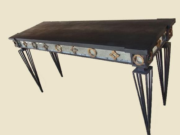 Two chic 1940s style French consoles in the Mid-Century Modern neoclassical taste of Gilbert Poillerat. The structure is in wrought iron with sharply tapering legs and with a mirrored apron featuring decoration with gilt circular and star forms.