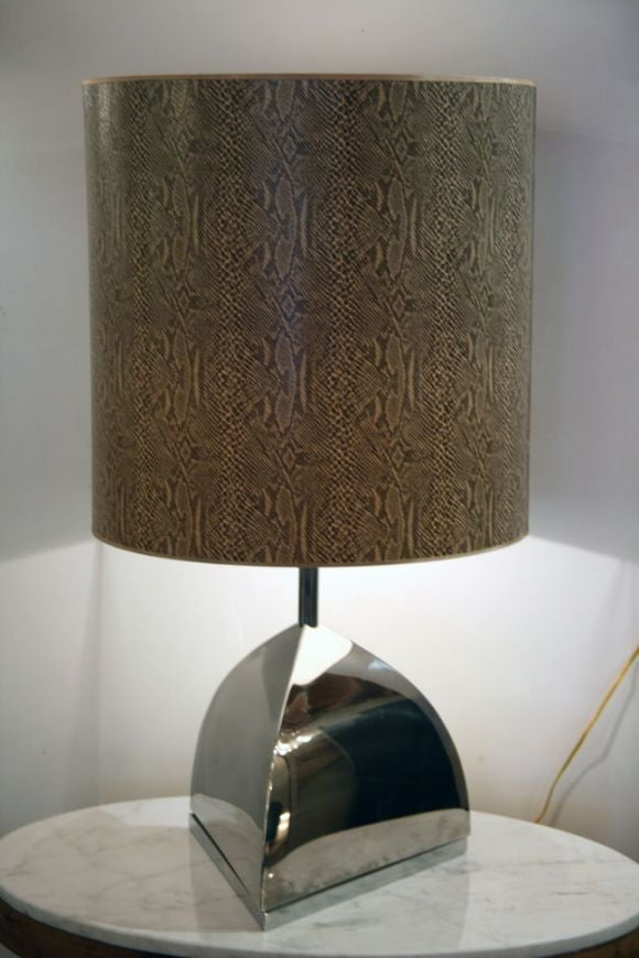 Steel triangle shaped table lamp with snake skin shade.