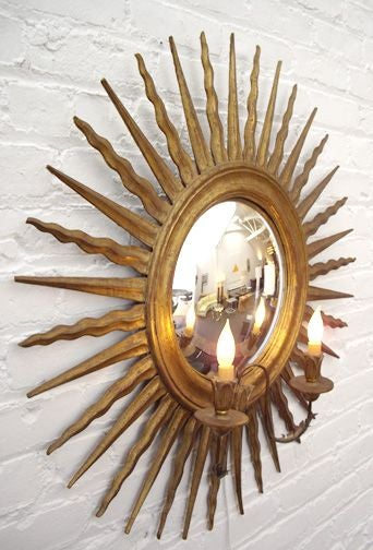 Italian starburst mirror and sconce with gilt carved wood frame. Features two electrified candles. The mirror is convex. Top quality design and construction.