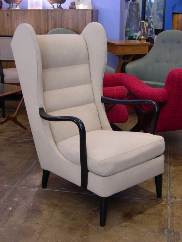 Single Swedish modernist wing back chair in ebonized elm ca. 1950.<br /> Restored and recovered in textured cream colored ultra suede.