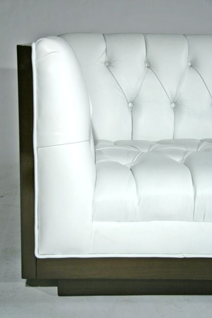 Tufted white leather sofa with walnut case by Milo