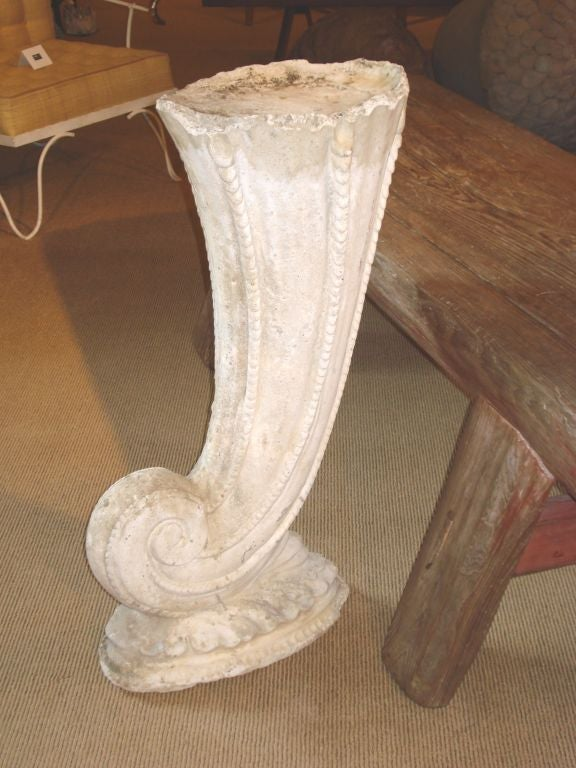 A cast concrete elongated shell, forming a pedestal as it rests on a