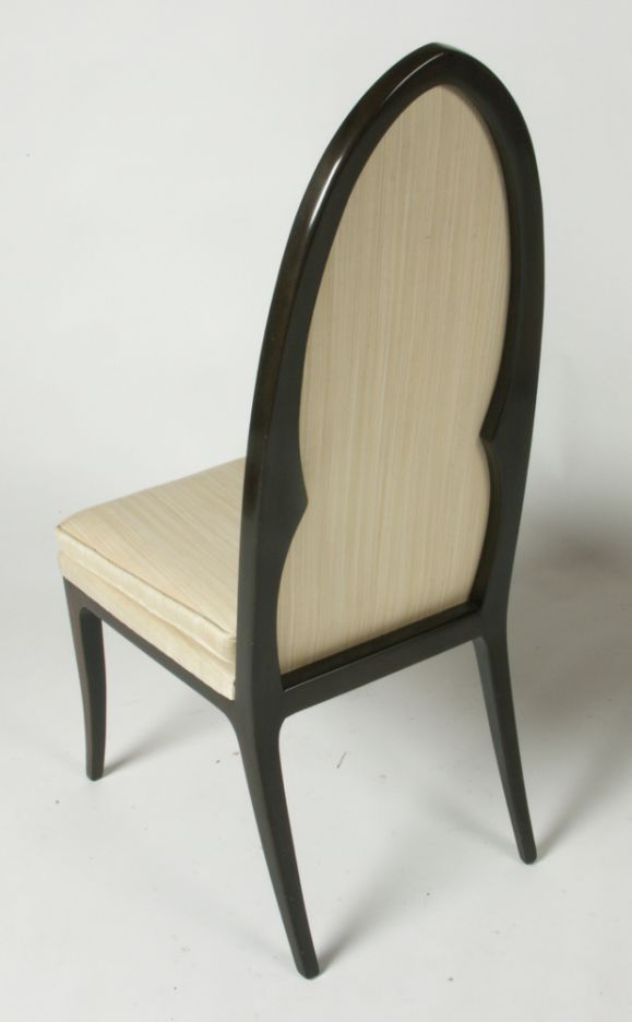 Pair of high arch back side chairs in dark mahogany with beige upholstery.