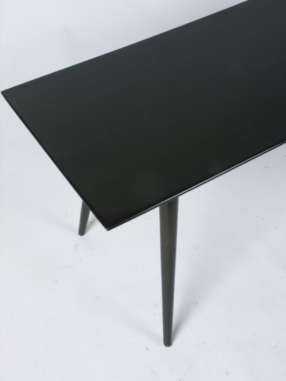 Dark finish on birch, 4 foot coffee table with angled tapered dowel legs. Measure: 60
